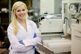 Photo of female co-op student posing in a lab coat